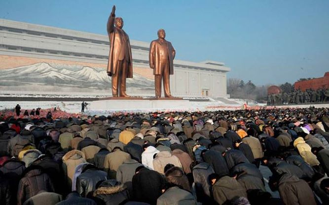North Koreans bow in front of bronze statues of North Korea founder Kim Il-sung and his son Kim Jong-il at Mansudae in Pyongyang